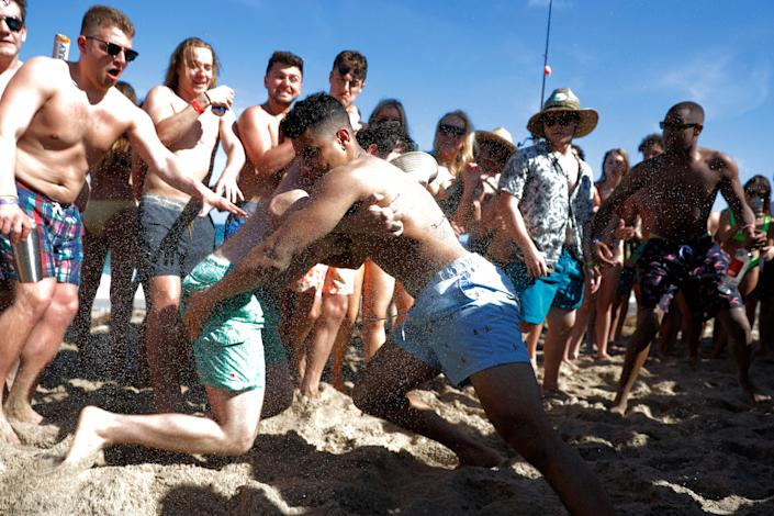 Two men wrestle each other as spring break revelers look on during a contest on the beach, Tuesday, March 17, 2020, in Pompano Beach, Fla.