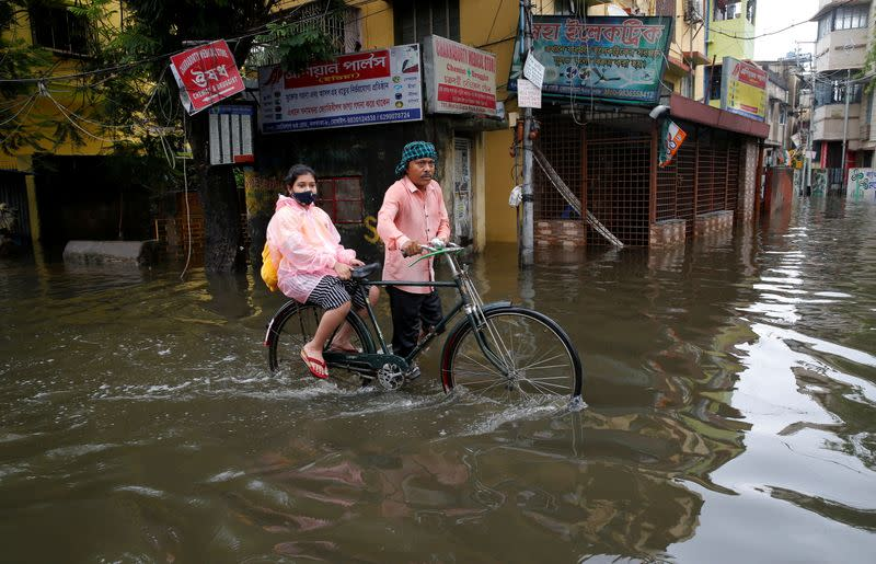 A man carries his daughter on a bicycle through a water-logged road after heavy rains in Kolkata