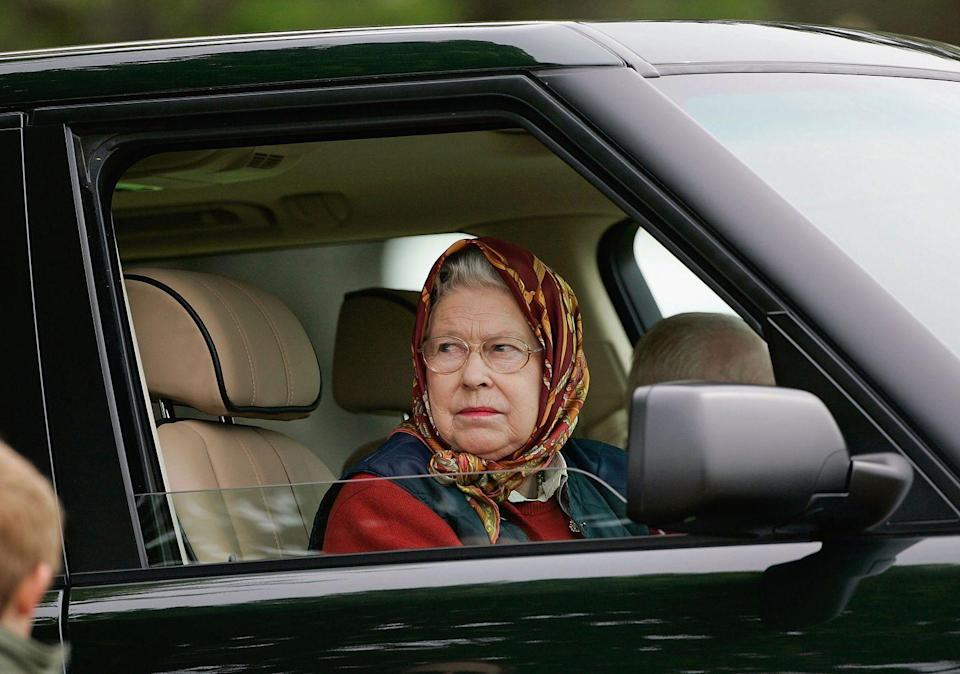 <p>A headscarf and Range Rover are Queen Elizabeth's Royal Windsor Horse Show essentials. The monarch drove to the 2005 show wearing maroon tones. </p>