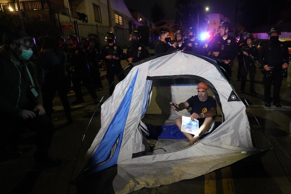 A demonstrator sets up a tent in front of police in the Echo Park section of Los Angeles Thursday, March 25, 2021. Demonstrators gathered Wednesday night to protest the planned temporary closure of a Los Angeles park that would displace a large homeless encampment, which has grown throughout the coronavirus pandemic. (AP Photo/Marcio Jose Sanchez)