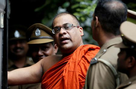 FILE PHOTO: Galagoda Aththe Gnanasara Thero, head of Buddhist group Bodu Bala Sena (BBS), walks towards a prison bus while accompanied by prison officers after he was sentenced by a court in Sri Lanka. June 14, 2018. REUTERS/Dinuka Liyanawatte/File Photo