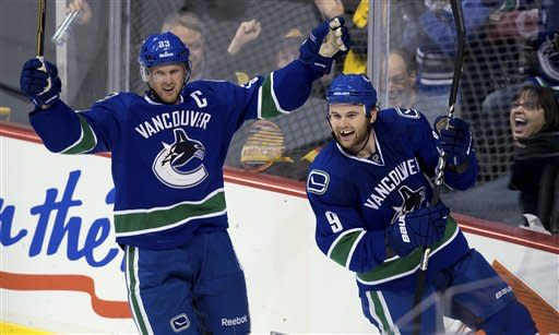 Vancouver Canucks' Henrik Sedin, left, of Sweden, and Zack Kassian celebrate Kassian's goal against the Edmonton Oilers during the second period of an NHL hockey game in Vancouver, British Columbia, on Sunday, Jan. 20, 2013. (AP Photo/The Canadian Press, Darryl Dyck)