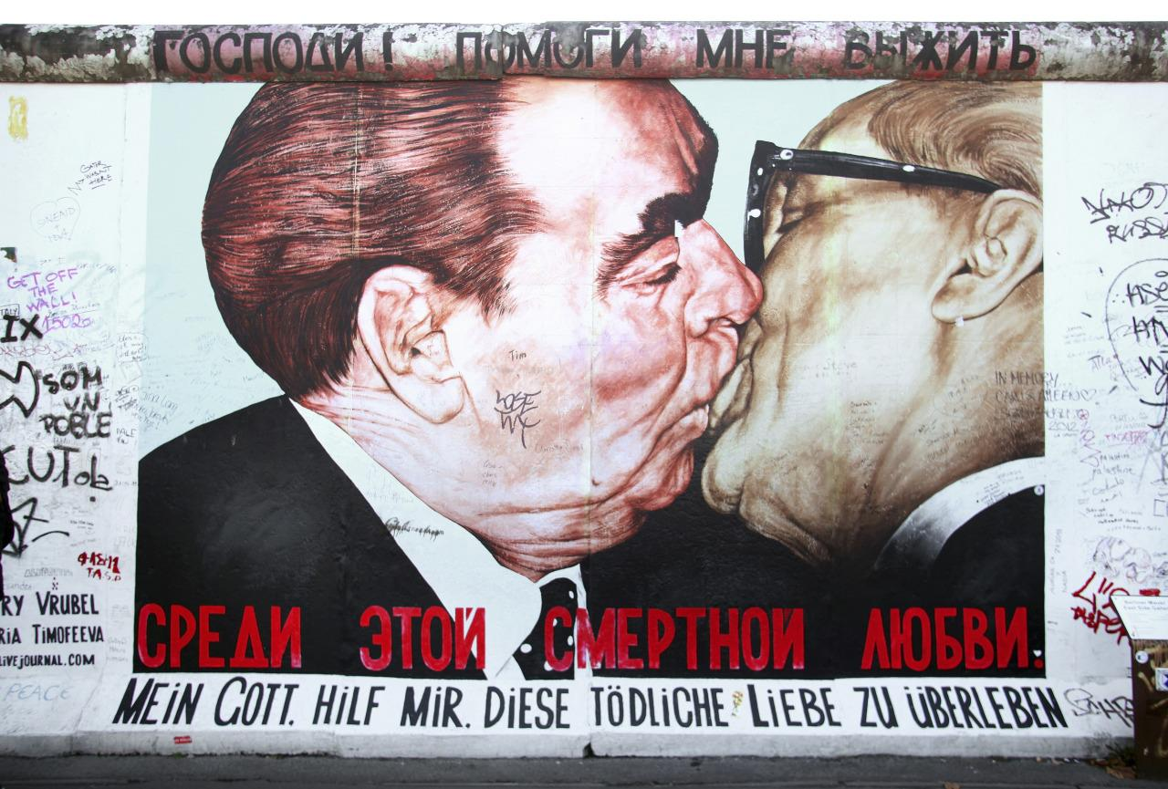 "<p>In honour of the 30th anniversary of the German Democratic Republic in 1979, Soviet leader Leonid Brezhnev and East German President Erich Honecker famously shared a ""fraternal kiss"". There was a Dmitri Vrubel murial of this moment on the Berlin Wall (shown here). <i>[Photo: Rex]</i><br /></p>"