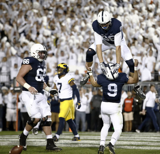 "Penn State's Mike Gesicki (88) celebrates by jumping over quarterback <a class=""link rapid-noclick-resp"" href=""/ncaaf/players/243269/"" data-ylk=""slk:Trace McSorley"">Trace McSorley</a> (9) after McSorley scored a touchdown against Michigan during the first half of an NCAA college football game in State College, Pa., Saturday, Oct. 21, 2017. (AP Photo/Chris Knight)"