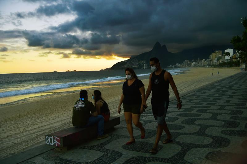 People wear face masks as a preventive measure against the novel coronavirus, COVID-19, as they walk along Ipanema Beach in Rio de Janeiro on May 19, 2020. - The novel coronavirus has killed at least 320,255 people worldwide since the outbreak first emerged in China last December, according to a tally from official sources compiled by AFP at 1900 GMT Tuesday. (Photo by Carl DE SOUZA / AFP) (Photo by CARL DE SOUZA/AFP via Getty Images)