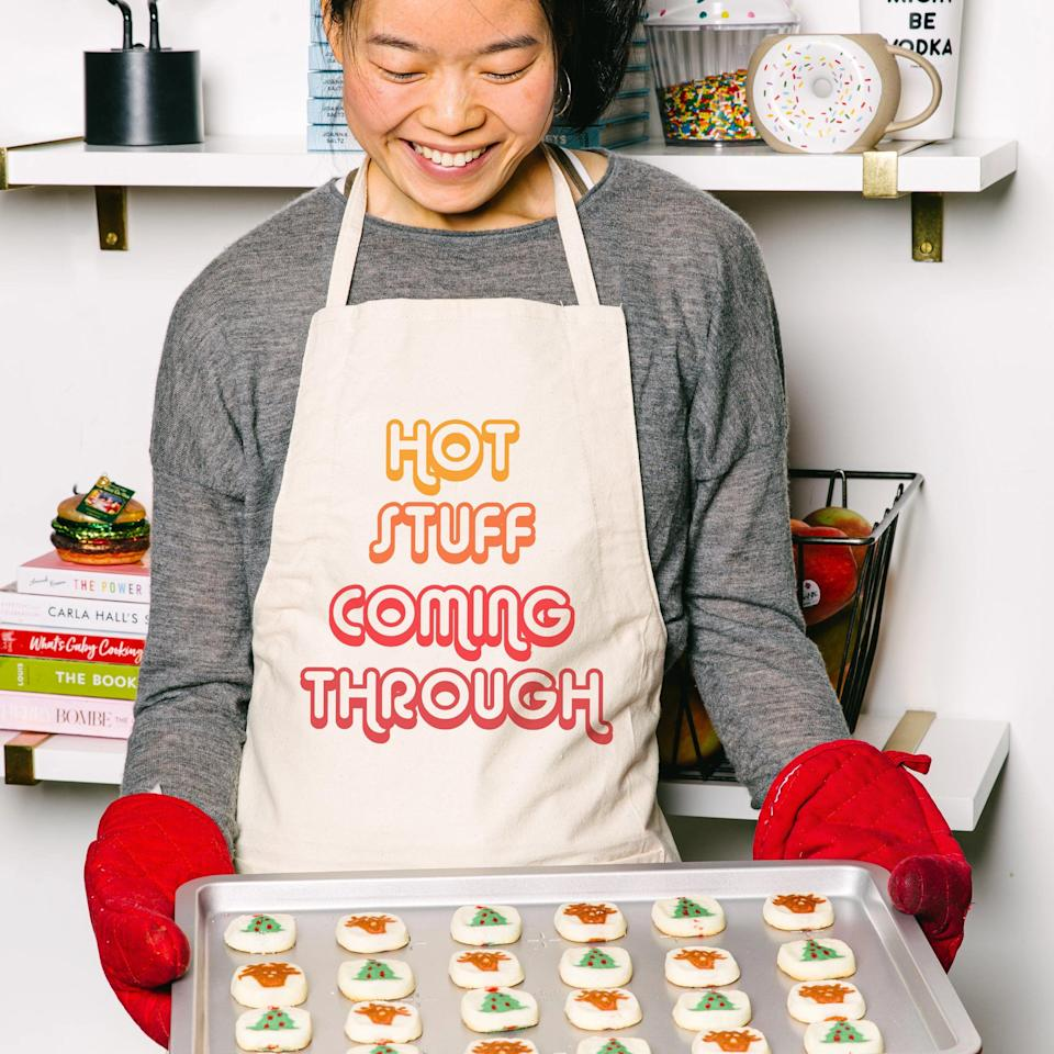"""<p>delish.com</p><p><strong>$25.00</strong></p><p><a href=""""https://shop.delish.com/products/hot-stuff-coming-through-apron"""" rel=""""nofollow noopener"""" target=""""_blank"""" data-ylk=""""slk:BUY NOW"""" class=""""link rapid-noclick-resp"""">BUY NOW</a></p><p>Protect your clothes in style with this fun apron. </p><p><strong>See more on <a href=""""https://shop.delish.com/"""" rel=""""nofollow noopener"""" target=""""_blank"""" data-ylk=""""slk:shop.delish.com"""" class=""""link rapid-noclick-resp"""">shop.delish.com</a>. </strong></p>"""