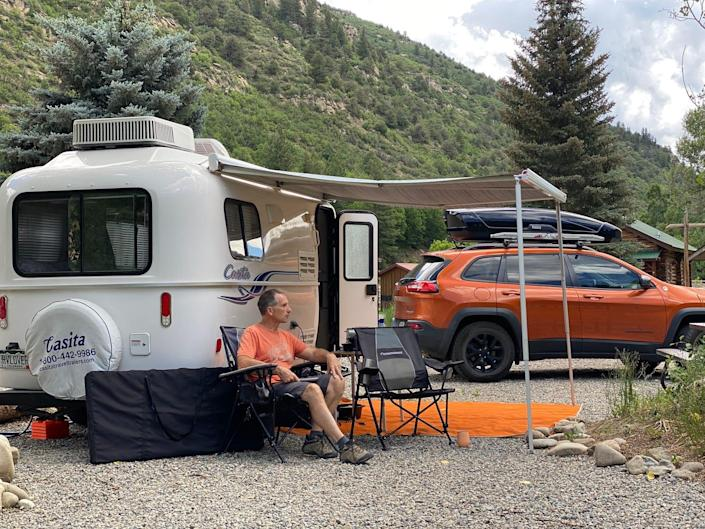 Marc sits at a campsite with his trailer and vehicle. There are mountains and trees behind him. Arrows point to essentials