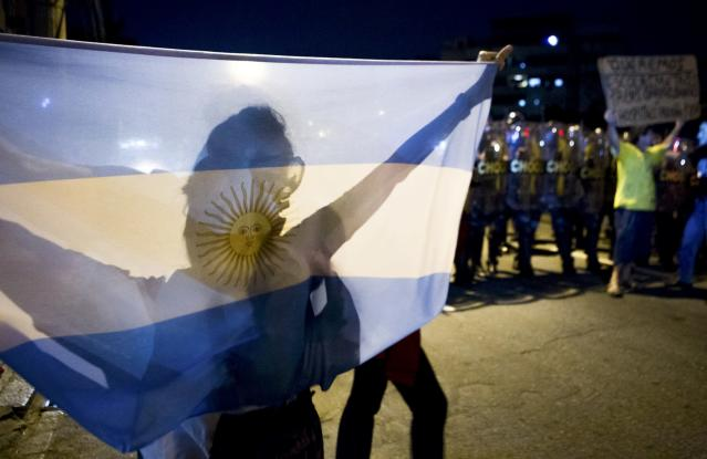 A protester holds up an Argentine flag during a demonstration against the public spending for the 2014 World Cup, in Rio de Janeiro June 15, 2014. Police blocked the streets to keep demonstrators from reaching Maracana soccer stadium as Argentina played Bosnia and Herzegovina for Group F. REUTERS/Stringer/Brazil/Marco Bello (BRAZIL - Tags: SPORT SOCCER WORLD CUP CIVIL UNREST POLITICS)