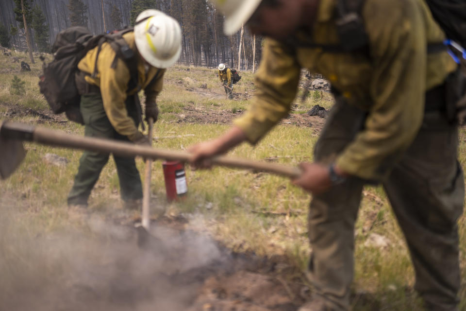 A firefighting crew from New Mexico mops up spot fires near the Northwest edge of the Bootleg Fire on Friday, July 23, 2021, near Paisley, Ore. (AP Photo/Nathan Howard)