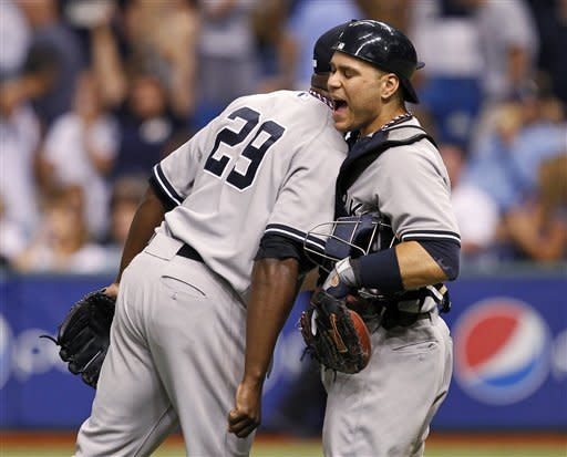 New York Yankees relief pitcher Rafael Soriano (29) celebrates a save with catcher Russell Martin after a baseball game against the Tampa Bay Rays, Wednesday, July 4, 2012, in St. Petersburg, Fla. The Yankees won 4-3. (AP Photo/Mike Carlson)