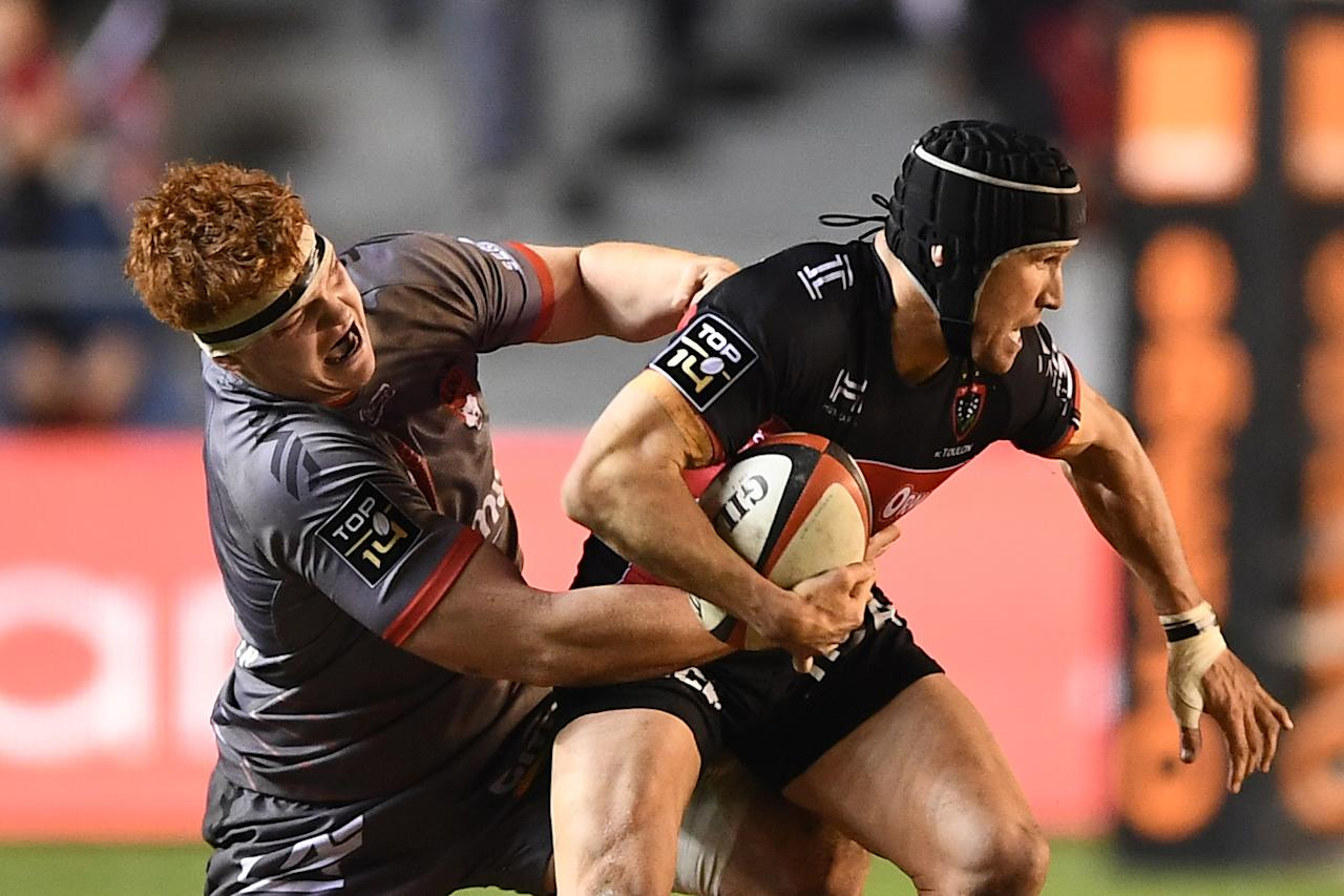 RC Toulon's Australian centre Matt Giteau (R) vies for the ball with Lyon's French lock Felix Lambey (L) during the French Top 14 rugby union match RC Toulon vs Lyon OU on February 18, 2017 at the Mayol stadium in Toulon, southern France. (AFP Photo/BORIS HORVAT)