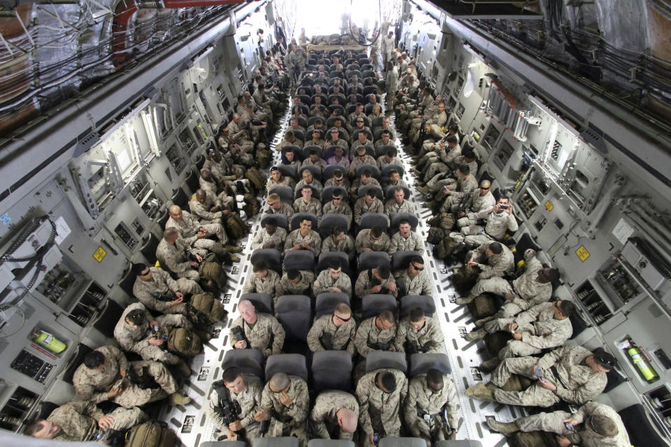 U.S. servicemen sit after boarding a transport plane before leaving for Afghanistan at the U.S. transit center at Manas airport near Bishkek, March 27, 2012.  REUTERS/Vladimir Pirogov  (KYRGYZSTAN - Tags: MILITARY TRANSPORT TPX IMAGES OF THE DAY) FOR BEST QUALITY IMAGE ALSO SEE: GM1E8BD1HEV01