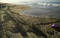 Oil is seen on the beach in Huntington Beach, California on October 3, 2021, after a pipeline breach connected to an oil rig off shore started leaking oil, according to an Orange County Supervisor (AFP/Patrick T. FALLON)