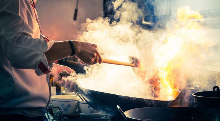 A person cooks something in a smoking wok