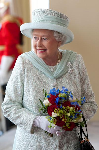 Britain's Queen Elizabeth II holds a bouquet of flowers as she returns to Buckingham Palace after attending a service of thanksgiving and a lunch in honour of the Diamond Jubilee in London,Tuesday June 5, 2012. (AP Photo/Carl Cort, Pool)