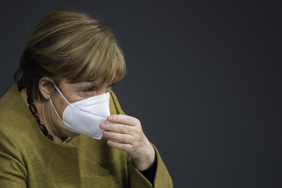 German Chancellor Angela Merkel adjusts her face mask as she attends a debate of the German Parliament Bundestag about the coronavirus outbreak situation in Berlin, Germany, Thursday, March 4, 2021. (AP Photo/Markus Schreiber)