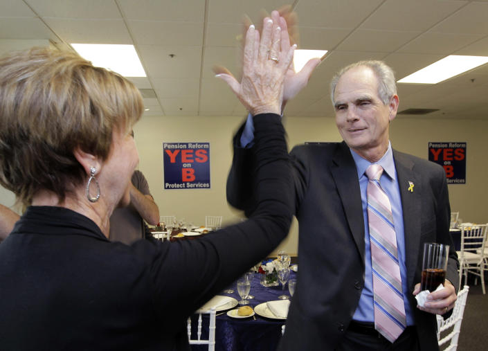 FILE - In this June 5, 2012 file photo, San Jose Mayor Chuck Reed, right, high fives former San Jose Vice Mayor Pat Dando as they arrive at a campaign party in San Jose, Calif. For years, companies have been chipping away at workers' pensions. Now, two California cities may help pave the way for governments to follow suit. Voters in San Diego and San Jose, the nation's eighth- and 10th-largest cities, overwhelmingly approved ballot measures last week to roll back municipal retirement benefits — and not just for future hires but for current employees. (AP Photo/Paul Sakuma, File)