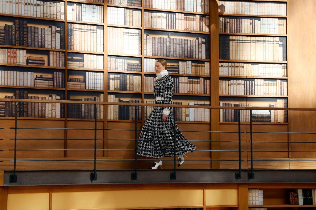 """<p>As a tribute to book lovers and house icons Coco Chanel and Karl Lagerfeld, Chanel transformed the Grand Palais into a multi-floor library for its Haute Couture Fall 2019 show. The runway saw models wearing tweed overcoats, skirt suits, puffed sleeves, and wire-framed spectacles. <em>CR </em>girl <a href=""""https://www.crfashionbook.com/fashion/g12240681/kaia-gerber-first-fashion-week/"""" target=""""_blank"""">Kaia Gerber</a> and others walked the show in Edwardian silhouettes, decorated with minimal embroidery and feathers. Ending on a feminine note, the show closed with a pastel pink tiered set, underscoring creative director Virginie Viard's elegant and charming vision.<em></em></p>"""