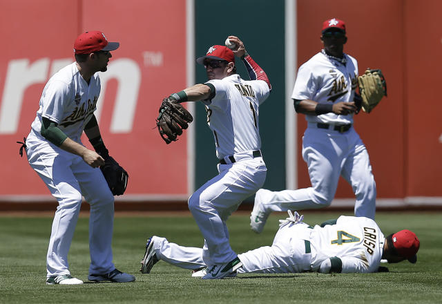 Oakland Athletics' Nick Punto, second from left, fields a ball hit by Toronto Blue Jays' Steve Tolleson in the fifth inning of a baseball game on Friday, July 4, 2014, in Oakland, Calif. Athletics' Jed Lowrie, left, Coco Crisp (4) and Yoenis Cespedes, third from left, assist on the play. (AP Photo/Ben Margot)