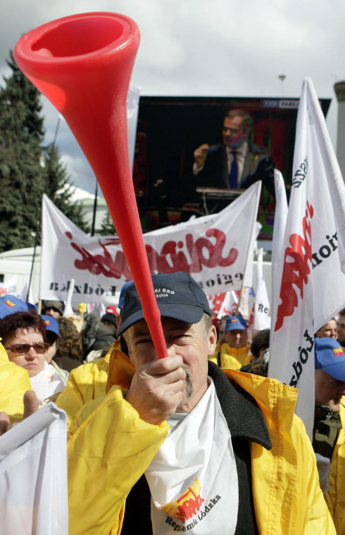 Polish workers protesting a government plan to raise retirement age to 67, turn their backs to a screen showing Prime Minister Donald Tusk speaking about the plan in Parliament, in Warsaw, Poland on Friday, March 30, 2012. (AP Photo/Czarek Sokolowski)