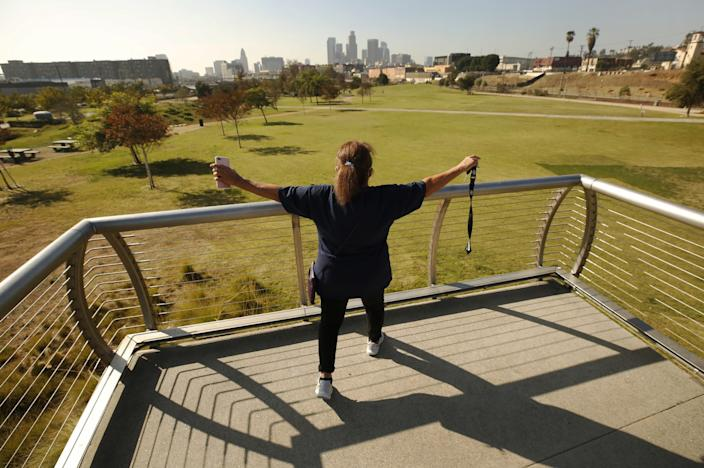 A woman stands on the pedestrian bridge overlooking Los Angeles State Historic Park with her arms outstretched