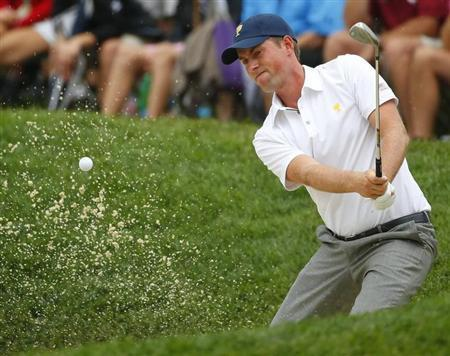 U.S. team member Webb Simpson hits from a bunker on the 14th hole as he plays International player Louis Oosthuizen of South Africa during the Singles matches for the 2013 Presidents Cup golf tournament at Muirfield Village Golf Club in Dublin, Ohio October 6, 2013. REUTERS/Jeff Haynes
