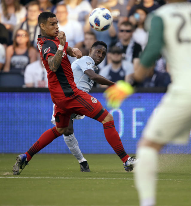 Sporting Kansas City forward Gerso, back, kicks on goal past Toronto FC defender Gregory van der Wiel, left, during the first half of an MLS soccer match in Kansas City, Kan., Saturday, July 7, 2018. (AP Photo/Orlin Wagner)