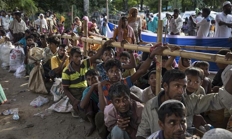 Rohingya people who have fled Myanmar wait for aid and transport to camps in Cox's Bazar, Bangladesh
