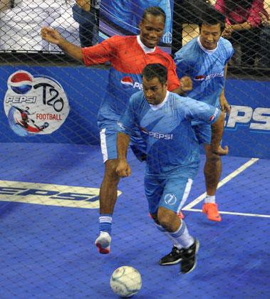 Indian cricket team captain MS Dhoni (front) tries to get the ball past International football player from the Ivory Coast, Didier Drogba  (L) while they play an exhibition match in New Delhi on June 17, 2012. Drogba is in the city for the grand finale of the Pepsi T20 football tournament.  AFP PHOTO/ SAJJAD HUSSAIN