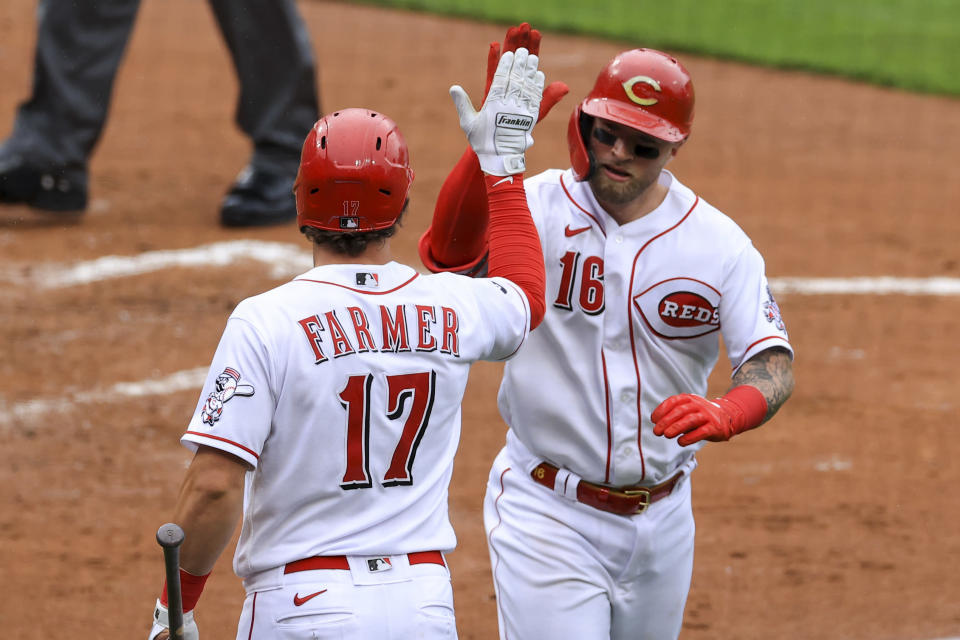 Cincinnati Reds' Kyle Farmer, left, celebrates a solo home run hit by Tucker Barnhart, right, during the second inning of a baseball game against the Cleveland Indians in Cincinnati, Saturday, April 17, 2021. (AP Photo/Aaron Doster)