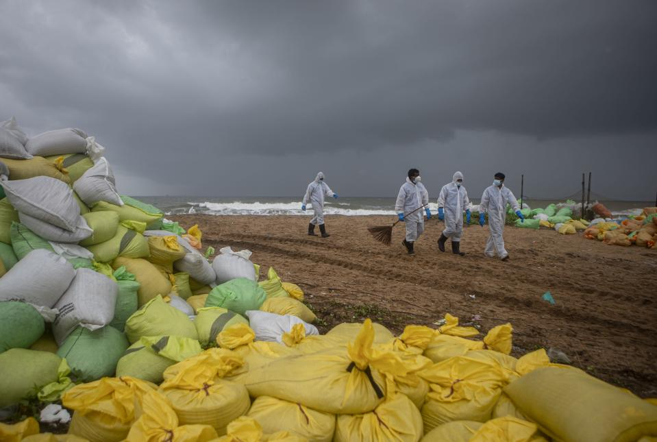 Sri Lankan navy soldiers walk on the beach looking for plastic debris washed ashore from fire damaged container ship MV X-Press Pearl at Kapungoda, on the outskirts of Colombo, Sri Lanka. Monday, June 14, 2021. (AP Photo/Eranga Jayawardena)
