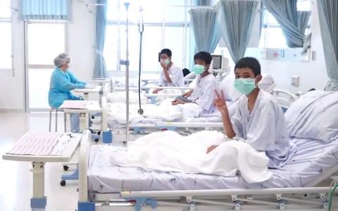 Three of the 12 boys are seen recovering in their hospital beds