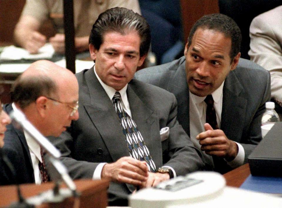 """LOS ANGELES, CA - MAY 3:  This 03 May, 1995 file photo shows murder defendant O.J. Simpson (R) consulting with friend Robert Kardashian (C) and Alvin Michelson (L), the attorney representing Kardashian, during a hearing in Los Angeles.  It was announced 02 October, 2003 that Kardashian, a businessman and lawyer who was a key figure in the O.J. Simpson saga and part of his legal """"dream team,"""" has died in Los Angeles from cancer of the esophagus.  He was 59 years old.  (Photo credit should read VINCE BUCCI/AFP via Getty Images)"""
