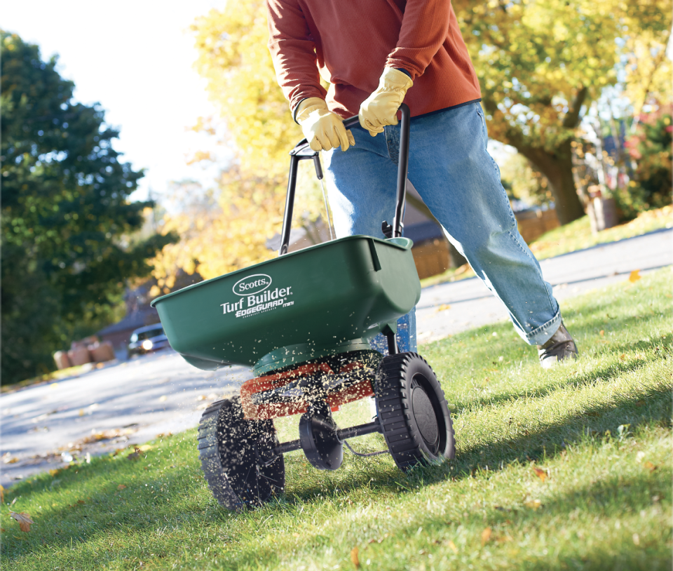 Person using a spreader to fertilize their lawn