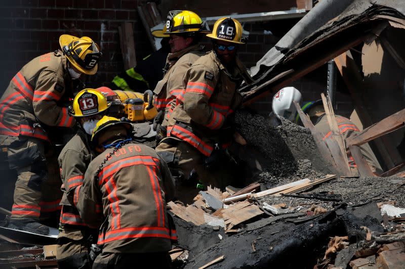 Fire fighters look for survivors at the scene of an explosion in a residential area of Baltimore