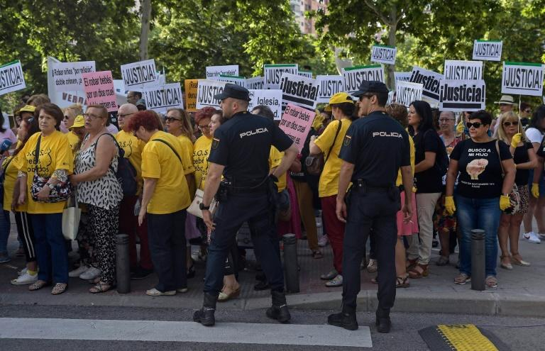 """Policemen stand in front of demonstrators holding placards reading """"Justice"""" outside the court where the trial over """"stolen babies"""" is looking at a practice that began in the 1950s after Franco came to power in Spain"""