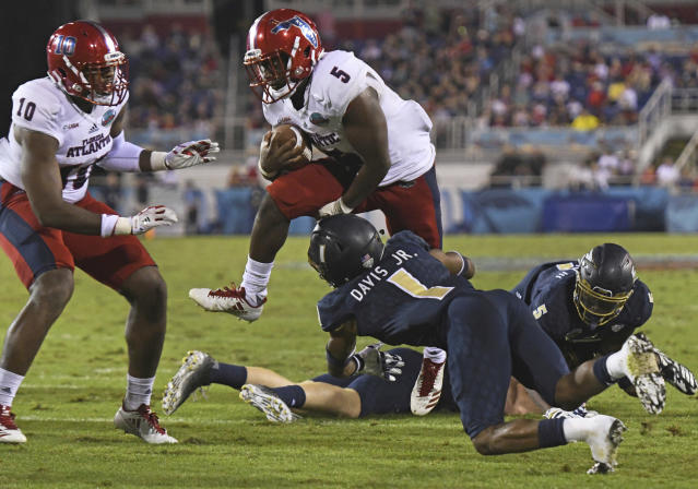 """Florida Atlantic running back <a class=""""link rapid-noclick-resp"""" href=""""/ncaaf/players/264882/"""" data-ylk=""""slk:Devin Singletary"""">Devin Singletary</a> (5) hurdles Akron cornerback <a class=""""link rapid-noclick-resp"""" href=""""/ncaaf/players/273737/"""" data-ylk=""""slk:Alvin Davis"""">Alvin Davis</a> (1) on his way to the end zone in the second quarter of an NCAA college football game in the Boca Raton Bowl in Boca Raton, Fla., Tuesday, Dec. 19, 2017. (Jim Rassol/South Florida Sun-Sentinel via AP)"""