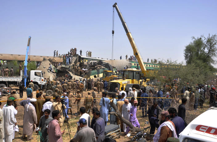 Soldiers use a crane to clear the track at the site of a train collision in the Ghotki district, southern Pakistan, Monday, June 7, 2021. Two express trains collided in southern Pakistan early Monday, killing dozens of passengers, authorities said, as rescuers and villagers worked to pull injured people and more bodies from the wreckage. (AP Photo/Waleed Saddique)
