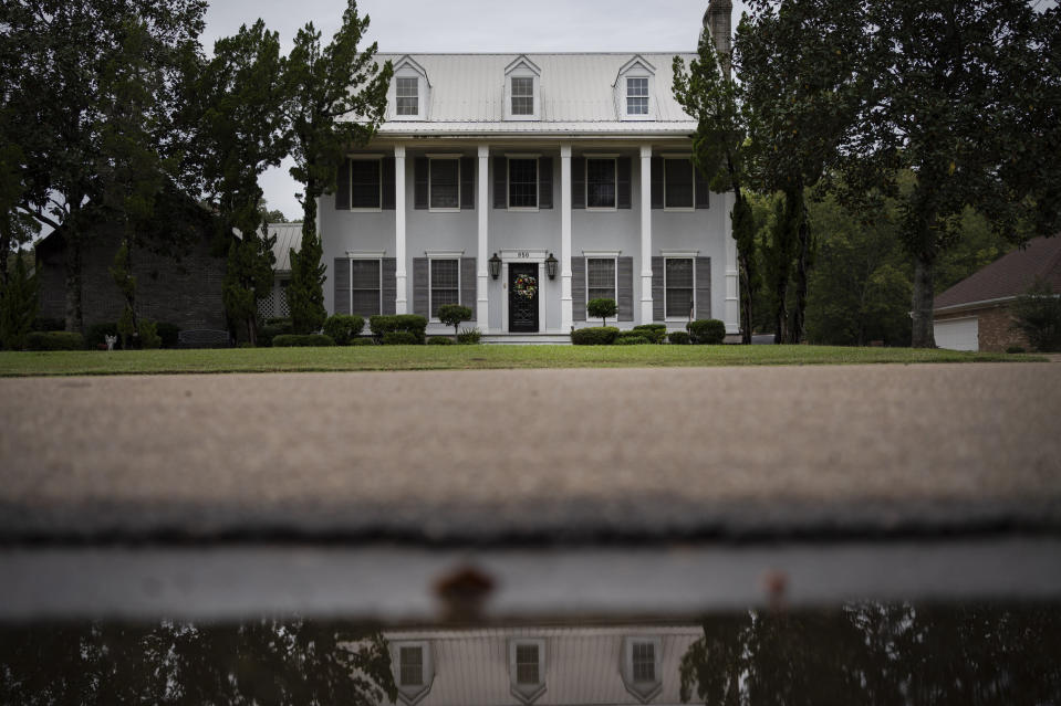 The house of Mike and Bonnie Bishop is reflected in a puddle, Friday, Oct. 9, 2020, in Byram, Miss. They met more than 25 years ago when she was organizing a basketball game to support an adopt-a-school program run by AT&T. She worked there until retiring a couple years ago. He still works there as a digital technician. (AP Photo/Wong Maye-E)