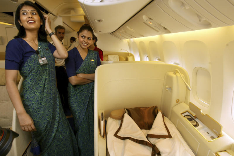FILE - In this July 30, 2007 file photo, Indian air cabin attendants explain the facilities available to First Class travelers in Air India's Boeing 777-200 LR passenger jet during an event to commemorate its commencement of operations, at the Chattrapati Shivaji International airport in Mumbai, India. India has become a hot ticket for international carriers since opening its airline industry to foreign investors last year. But the potential of a giant market where only a sliver of the population travel by plane also comes with a catch: airlines in India are vastly unprofitable thanks to sky-high costs and cut-throat competition. (AP Photo/Gautam Singh, file)