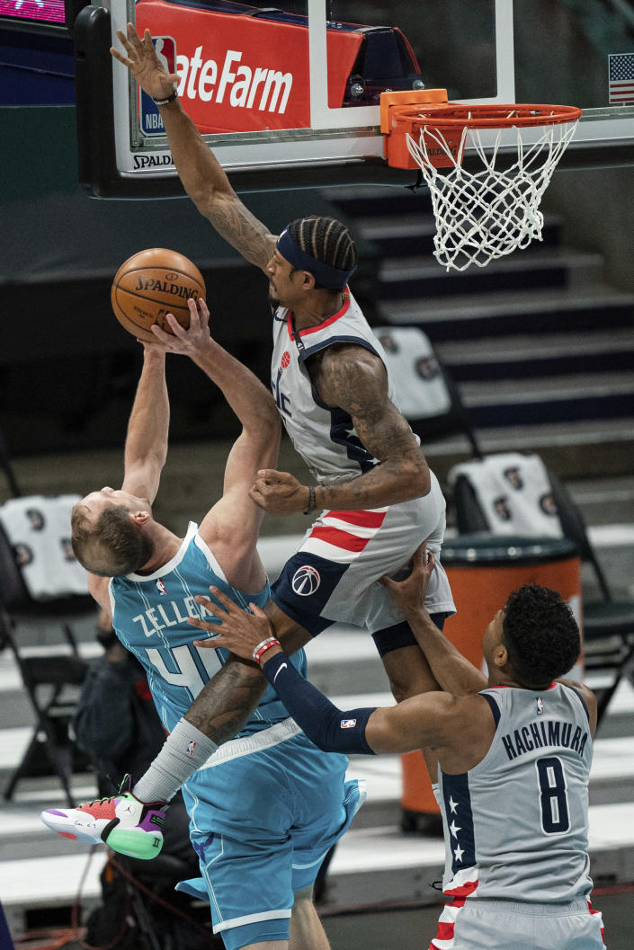 Washington Wizards guard Bradley Beal, top right, tries to block a shot from Charlotte Hornets center Cody Zeller (40) with Wizards forward Rui Hachimura (8) running in to help during the first half of an NBA basketball game in Charlotte, N.C., Sunday, Feb. 7, 2021. (AP Photo/Jacob Kupferman)