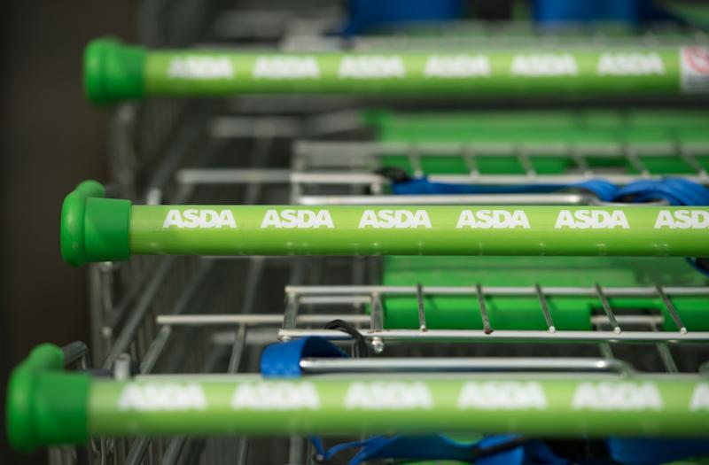 Logos of supermarket chain Asda are pictured on the handles of shopping trolleys outside a store in Stockport, northern England on April 30, 2018. - Britain's second and third biggest supermarket chains Sainsbury's and Walmart-owned Asda have agreed to merge, the pair said Monday, hoping to create a £13-billion ($18-billion, 15-billion-euro) retail king and leapfrog UK number one Tesco. The blockbuster deal -- which is effectively a takeover bid with Sainsbury's acquiring a majority 58-percent stake -- comes as the British supermarket sector faces squeezed profit margins and fierce competition from German-owned discounters Aldi and Lidl and online US titan Amazon. (Photo by Oli SCARFF / AFP) (Photo credit should read OLI SCARFF/AFP via Getty Images)