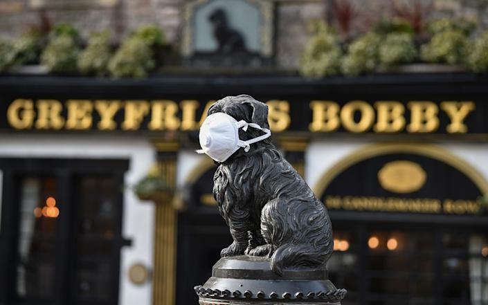 The Greyfriars Bobby statue has a face mask placed on its head in Edinburgh - Getty Images Europe