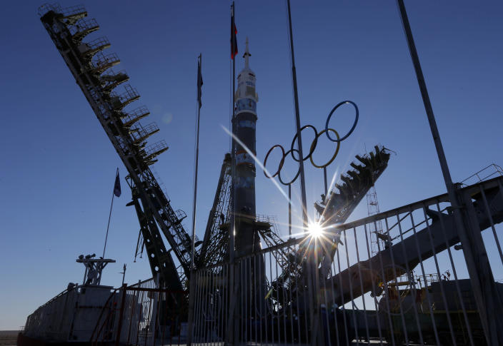 Service towers are lifted to Russia's Soyuz-FG booster rocket loaded with Soyuz TMA-11M space capsule that will carry new crew to the International Space Station (ISS) at the launch pad decorated with the Olympic rings at the Russian leased Baikonur cosmodrome, Kazakhstan, Tuesday, Nov. 5, 2013. For the first time, the rocket, emblazoned with the emblem of the Winter Olympics in Sochi, will carry an Olympic torch to space as part of the ongoing Olympic torch relay. The torch will be brought back along with the station's current crew. The rocket is scheduled to blast off on Thursday, Nov. 7. (AP Photo/Dmitry Lovetsky)