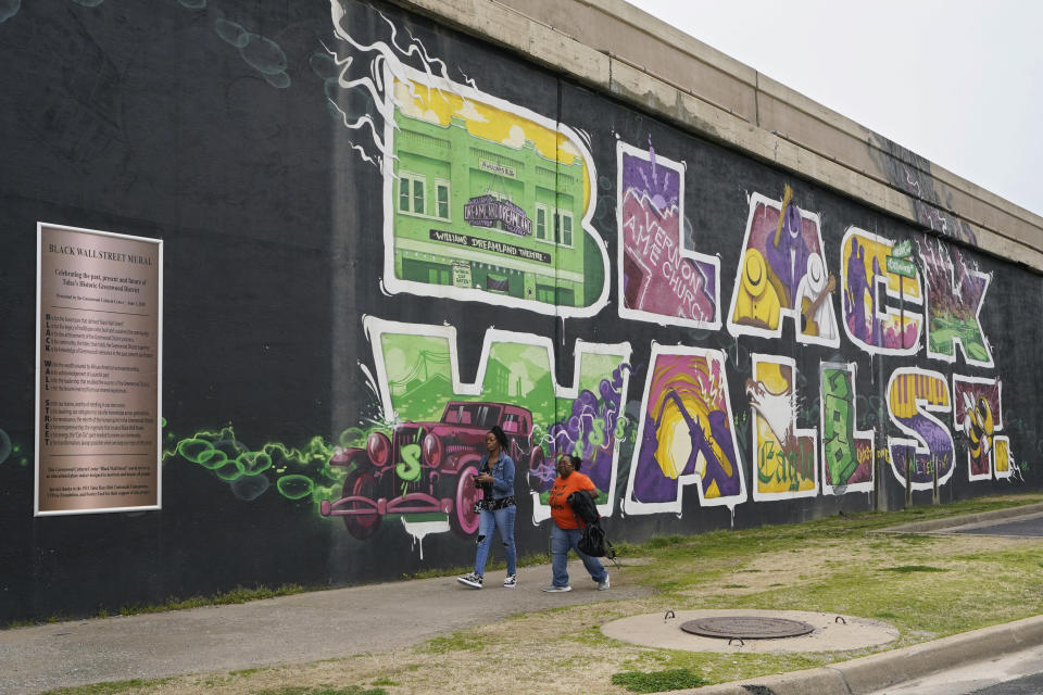 Javohn Perry, left, of Seattle, and her cousin, Danielle Johnson, right, of Beggs, Okla., walk past a mural commemorating Black Wall Street in Tulsa, Okla., on Monday, April 12, 2021. (AP Photo/Sue Ogrocki)