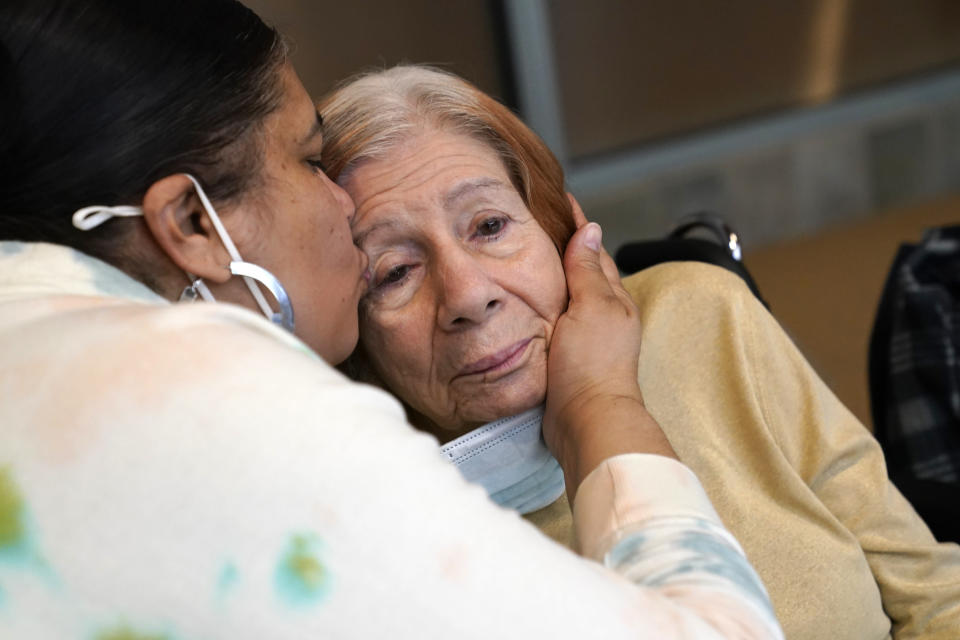 FILE - Rosa DeSoto, left, embraces her 93-year-old mother Gloria DeSoto, who suffers from dementia, inside the Hebrew Home at Riverdale, Sunday, March 28, 2021, in the Bronx borough of New York. It was the first time in over a year that residents' families were allowed to enter the nursing home for in-person visits allowing physical contact among loved ones. A focus on the elderly at the start of the nation's vaccination campaign helped protect nursing homes that were ravaged at the height of the U.S. coronavirus outbreak, but they are far from in the clear. New outbreaks, often traced to infected staff members, are still occurring in long-term care centers across the country, causing continued havoc for visitation policies. (AP Photo/Kathy Willens)