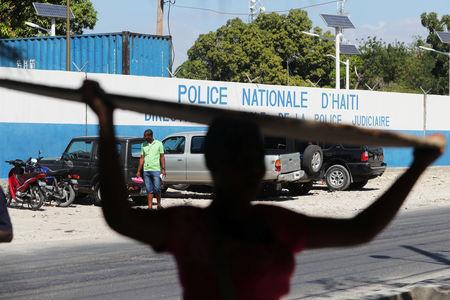 A woman carries a deck in front of a main Haitian police station, where according to local media a group of foreign nationals including Americans armed with semi-automatic weapons were detained, after anti-government protests, in Port-au-Prince, Haiti, February 18, 2019. REUTERS/Ivan Alvarado