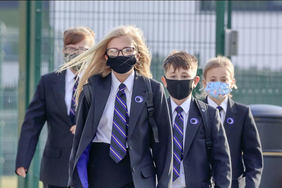 <p>Pupils wearing masks on their way to school</p> (PA)