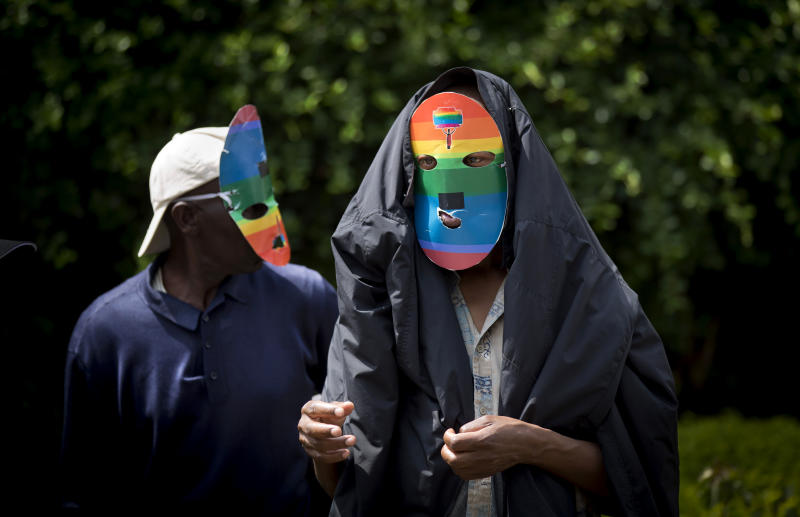 FILE - In this Feb. 10, 2014 file photo, Kenyan gays and lesbians and others supporting their cause wear masks to preserve their anonymity as they stage a rare protest, against Uganda's increasingly tough stance against homosexuality and in solidarity with their counterparts there, outside the Uganda High Commission in Nairobi, Kenya Monday, Feb. 10, 2014. Uganda's president Yoweri Museveni is expected to sign Monday, Feb. 24, 2014 a controversial anti-gay bill that allows harsh penalties for homosexual offenses, a bill which rights groups have condemned as draconian in a country where homosexuality is already illegal. (AP Photo/Ben Curtis, File)