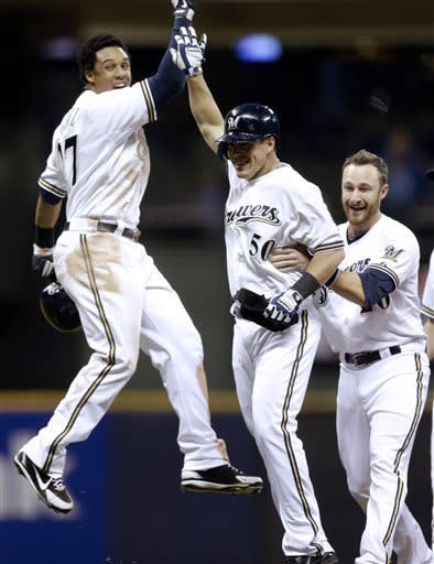 Milwaukee Brewers' Blake Lalli is congratulated by Carlos Gomez (27) and Jonathan Lucroy, right, after hitting a game-winning walk off single during the ninth inning of a baseball game against the San Francisco Giants Wednesday, April 17, 2013, in Milwaukee. The Brewers won 4-3. (AP Photo/Morry Gash)